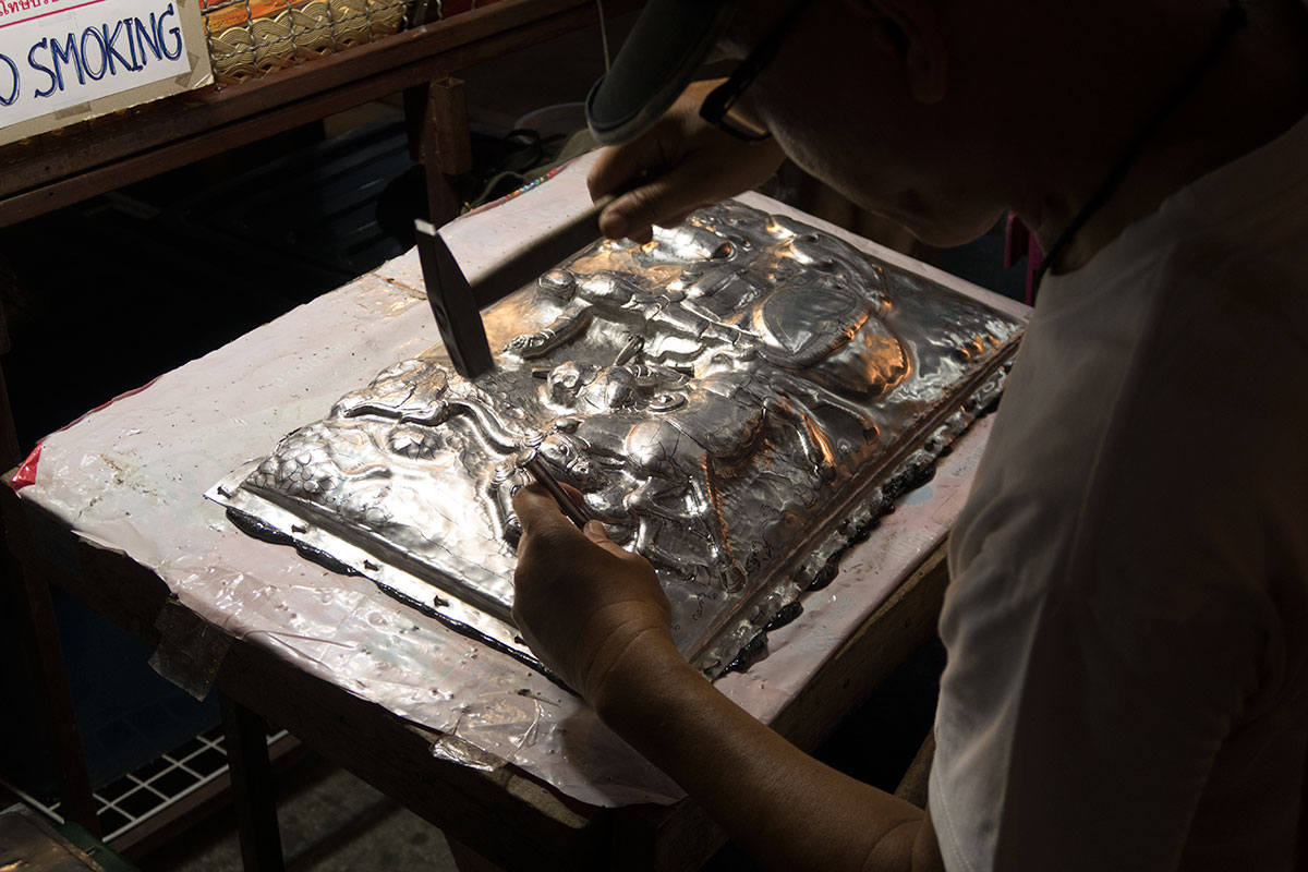 Artist working on metal
